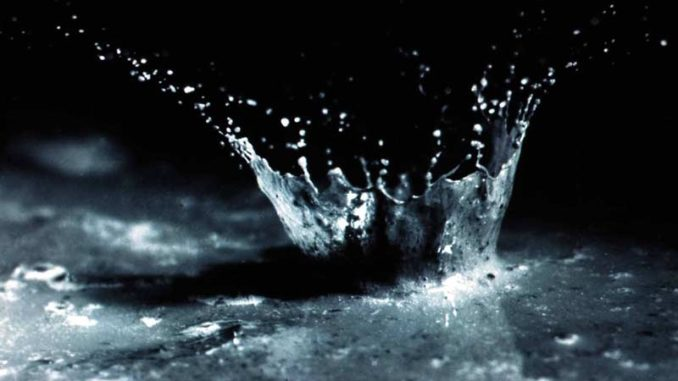 A close-up of water and soil being splashed by the impact of a single raindrop. USDA, public domain.