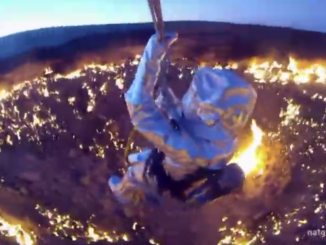 Wearing a heat-resistant aluminum suit and suspended on a wire above Darvaza gas crater, George Kourounis prepares to descend to the fiery floor of the pit.